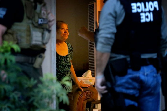 Immigration and Customs Enforcement officers looking for a fugitive migrant question his mother during a morning raid on his residence in Riverside.