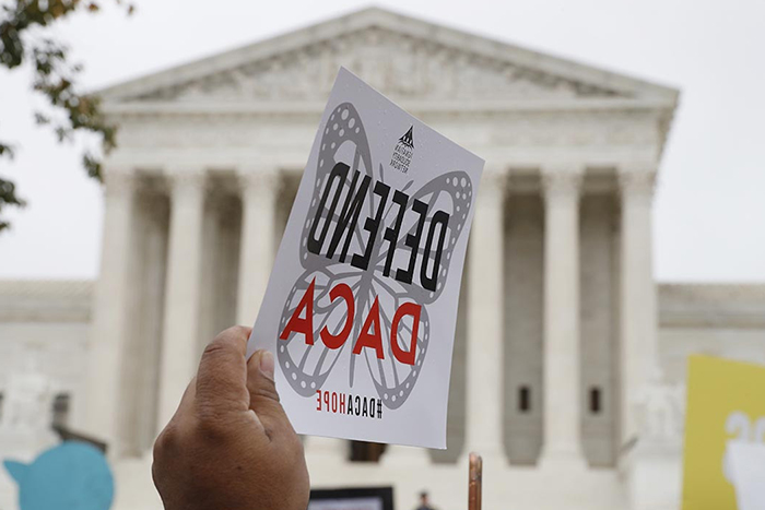 Supreme Court with a sign that says Defend DACA