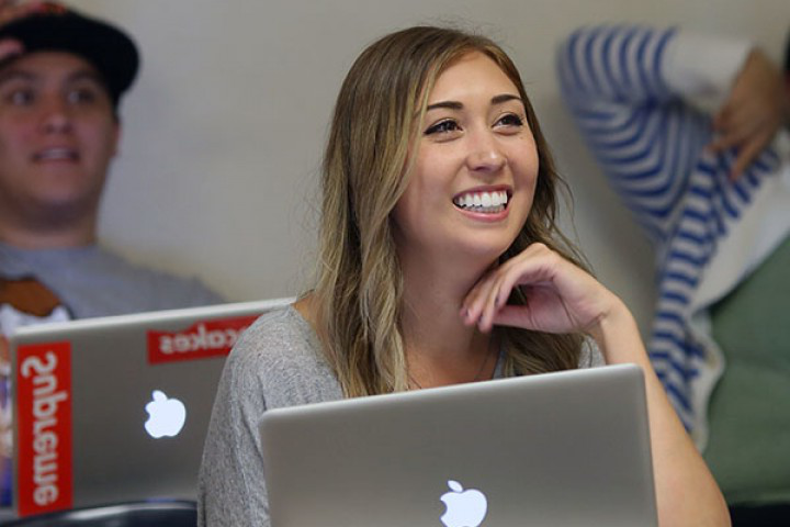 student with laptop smiling in classroom