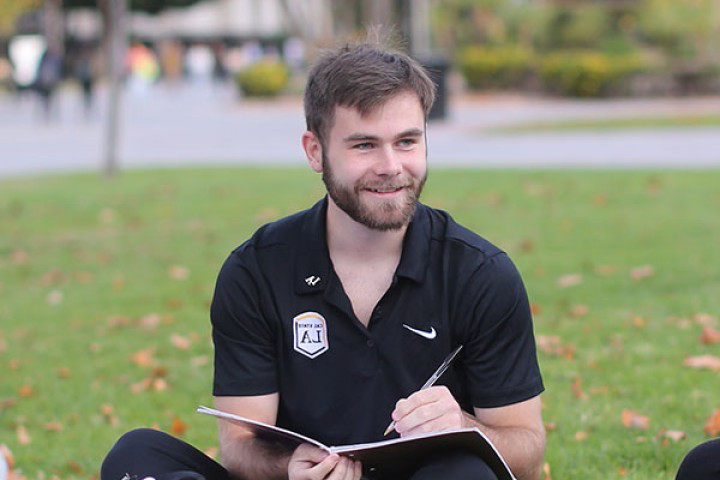 Student holding notebook and pen sitting on lawn
