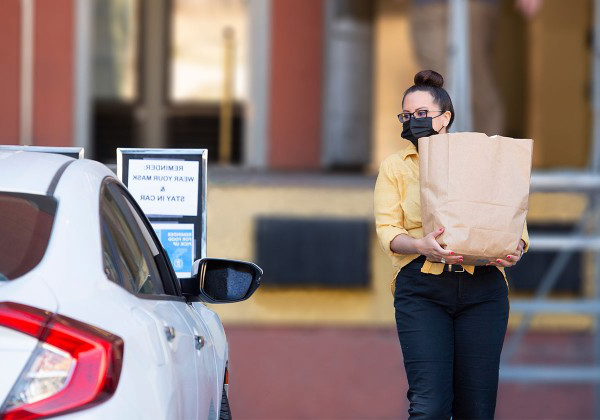 Staff member carries out bag of groceries